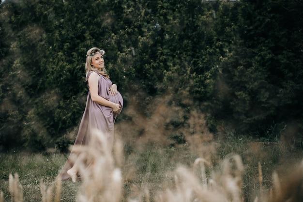 Zwangere vrouw die op het tarwegebied loopt Premium Foto