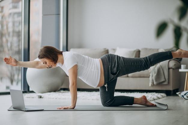 Zwangere vrouw die yoga thuis uitoefenen Gratis Foto