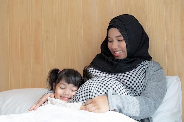 Zwangere vrouw en haar handen van de dochterholding op haar buik op het bed Premium Foto