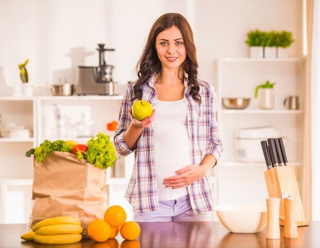 Zwangere vrouw in de keuken met groenten en fruit. Premium Foto