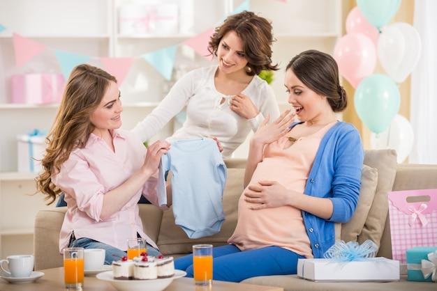 Zwangere vrouw is open een nieuw geschenk bij baby shower. Premium Foto