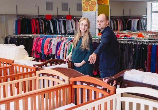 Zwangere vrouw met echtgenoot kiest een babybedje in de winkel. Premium Foto