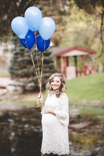 Zwangere vrouw met een witte jurk met ballonnen in een tuin onder zonlicht Gratis Foto