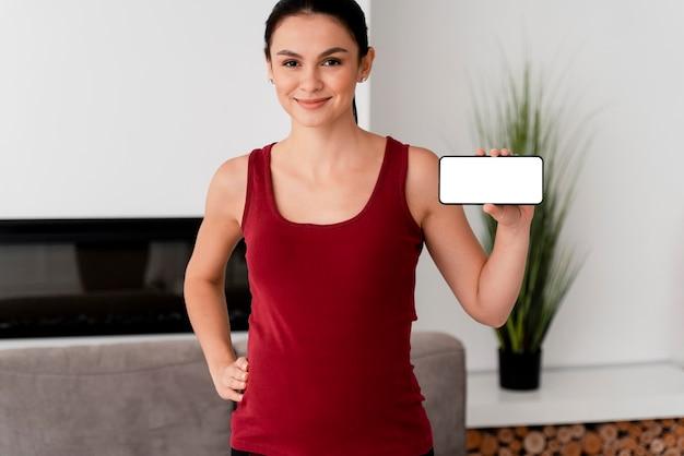 Zwangere vrouw met een witte kaart in haar hand Gratis Foto
