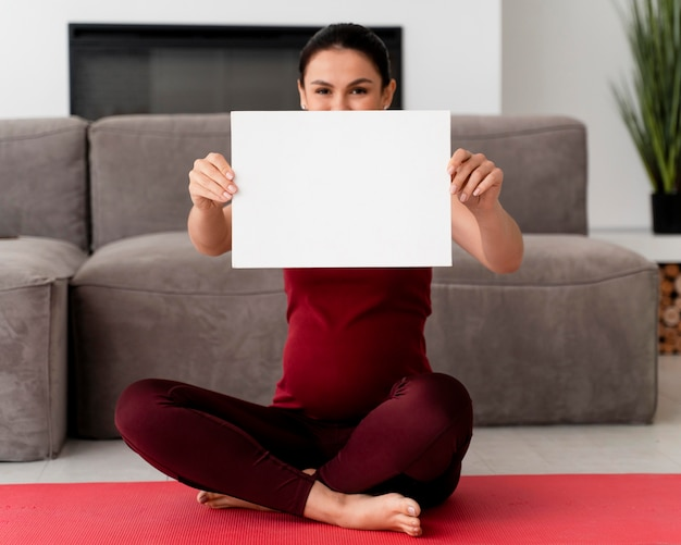 Zwangere vrouw met een witte kaart Gratis Foto