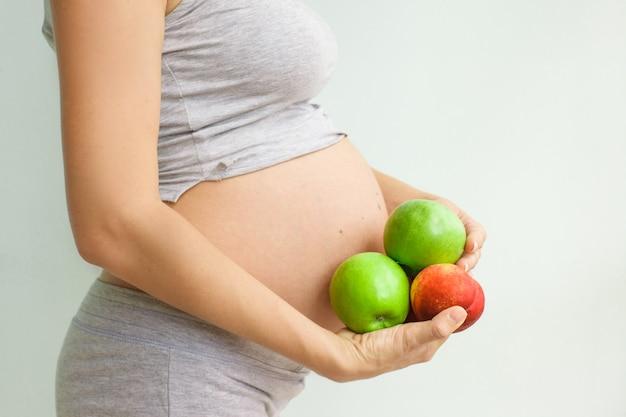 Zwangere vrouw met fruit in haar handen Premium Foto