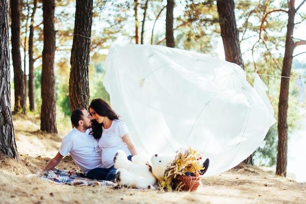 Zwangere vrouw met haar man op picknick Premium Foto