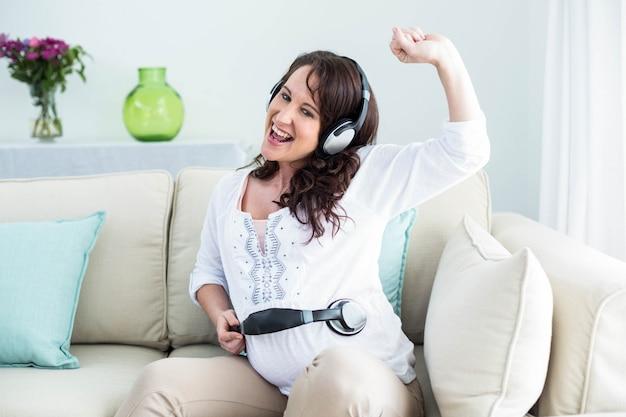 Zwangere vrouw met hoofdtelefoon op buik in de woonkamer Premium Foto