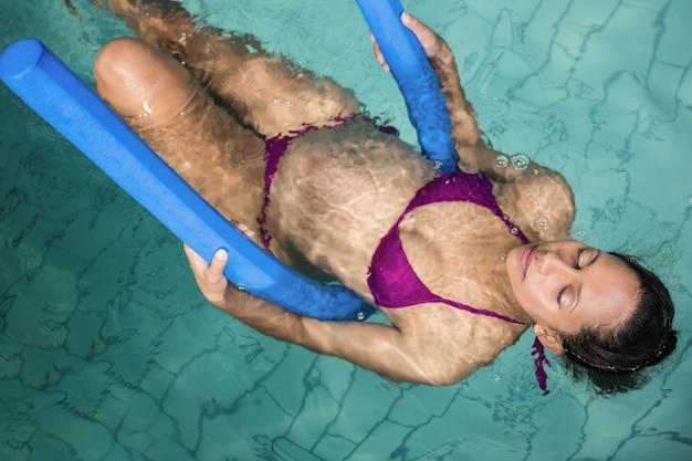 Zwangere vrouw met schuimrol in het zwembad Premium Foto