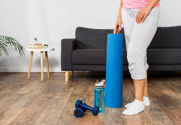 Zwangere vrouw thuis met waterfles en gewichten Gratis Foto