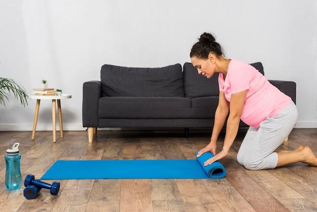 Zwangere vrouw thuis oefeningsmat oprollen Gratis Foto