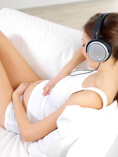 Zwangere vrouw zittend op een witte bank thuis en luisteren muziek in koptelefoon Gratis Foto