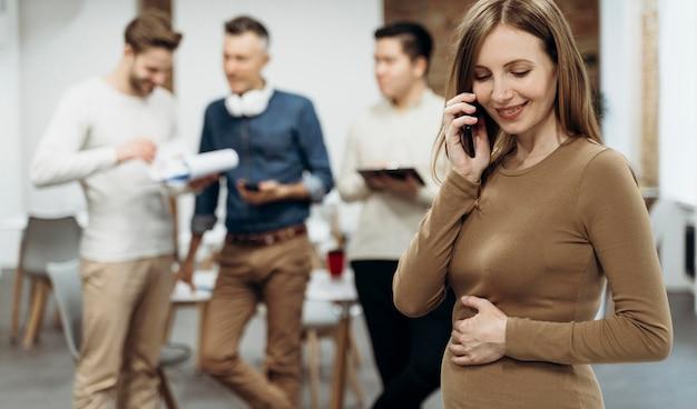 Zwangere zakenvrouw praten aan de telefoon terwijl ze haar buik aanraakt Gratis Foto