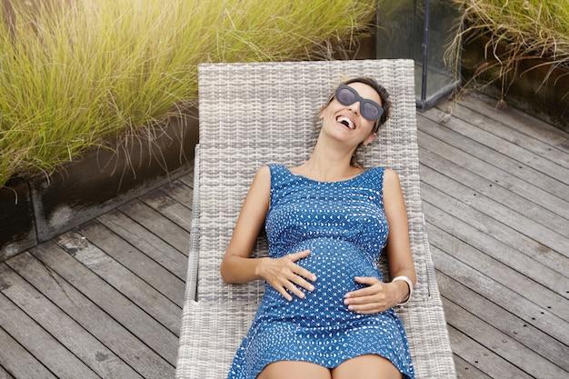 Zwangerschap en moederschap concept. bovenaanzicht van mooie gelukkig zwangere vrouw in tinten liggend op een ligstoel en haar buik aan te raken. Gratis Foto