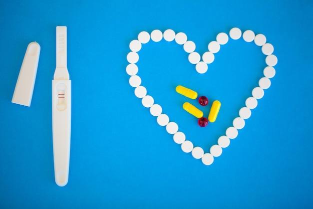 Zwangerschapstest positief met twee strepen en anticonceptiepil op blauw Premium Foto