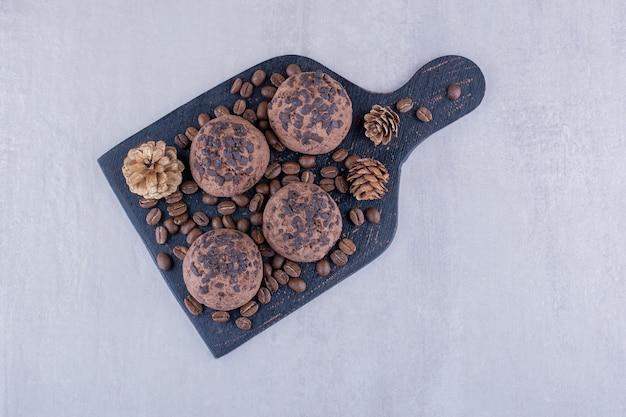 Zwart bord met koffiebonen, koekjes en dennenappels op witte achtergrond. Gratis Foto