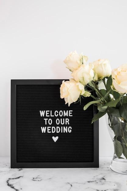 Zwart bord met welkom in onze trouwboodschap en rozenvaas op marmeren tafelblad Gratis Foto