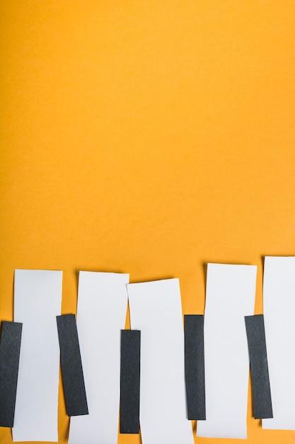 Zwart en wit papier gerangschikt in rij maken pianotoetsen op gele achtergrond Gratis Foto