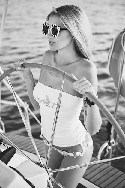 Zwart en wit portret van een blond modelmeisje met slank perfect lichaam in bikini en zonnebril houdt stuurwiel en poseren op een jachtschip Premium Foto
