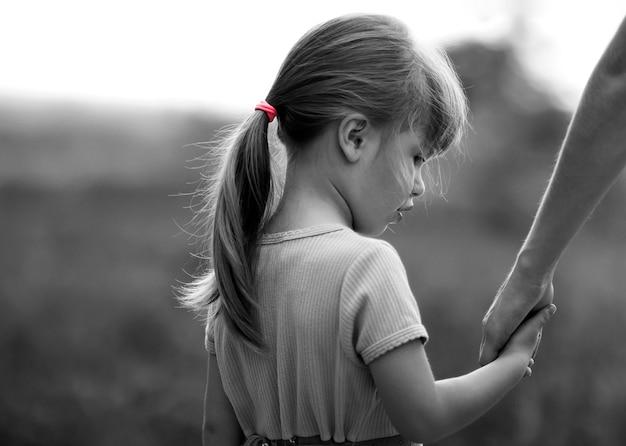 Zwart en wit portret van meisje dat een hand van haar moeder houdt Premium Foto