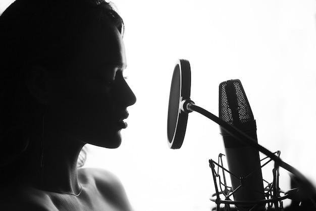 Zwart en wit. vrouw het zingen in de opnamestudio. Premium Foto