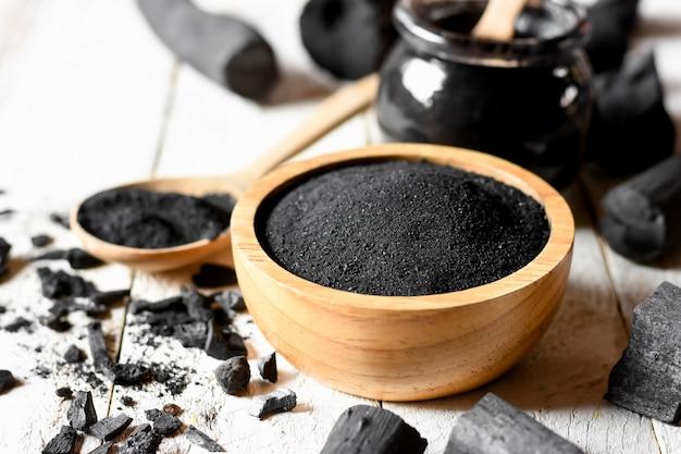 Zwart houtskoolpoeder voor gezichtsmasker en scrub. Premium Foto