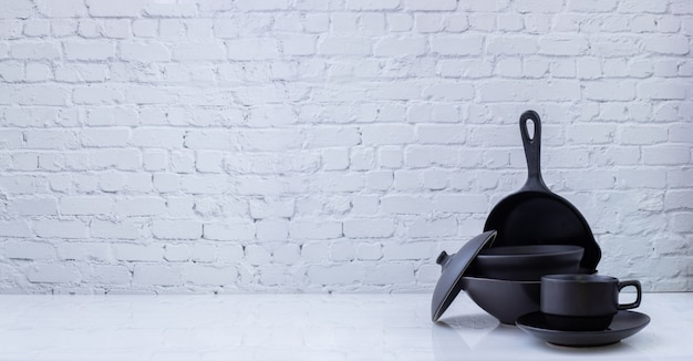 Zwart keukengerei op witte bakstenen muurtextuur Premium Foto