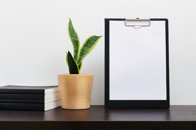 Zwart klembordmodel met cactus in een pot en boek op donkere werkruimtetafel en witte achtergrond Premium Foto