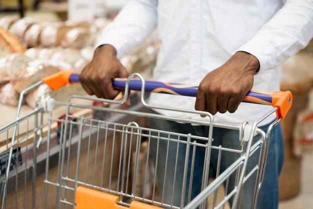Zwart mannetje dat brood kiest bij kruidenierswinkelopslag Gratis Foto