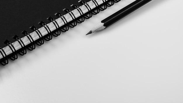 Zwart notitieboekje en een potlood op witte bureauachtergrond met exemplaarruimte Premium Foto