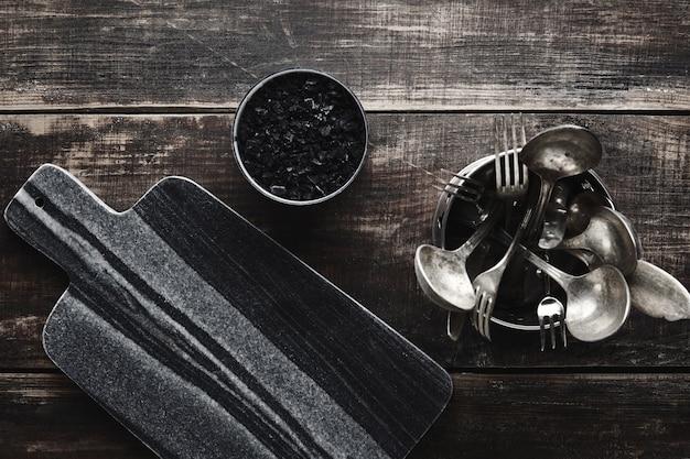 Zwart stenen marmeren snijbureau, vulcanozout en vintage keukengerei: vork, mes, lepel in stalen pot op verouderde houten tafel. bovenaanzicht. Gratis Foto