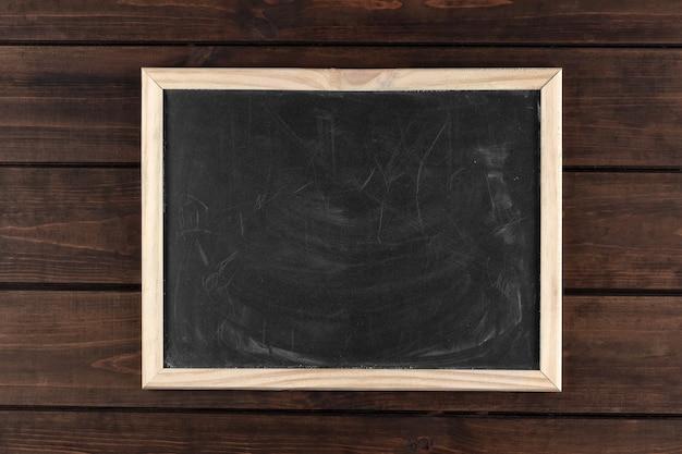 Zwart vuil schoolbord in een frame op een donkere houten achtergrond, kopie ruimte, bovenaanzicht Premium Foto