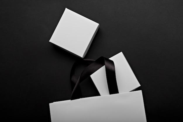 Zwart-wit foto van een witte papieren zak en dozen op een zwarte achtergrond. plaats voor uw logo-branding Premium Foto