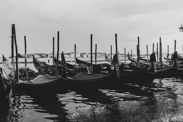 Zwart-wit schot van gondels aangemeerd in het water Gratis Foto