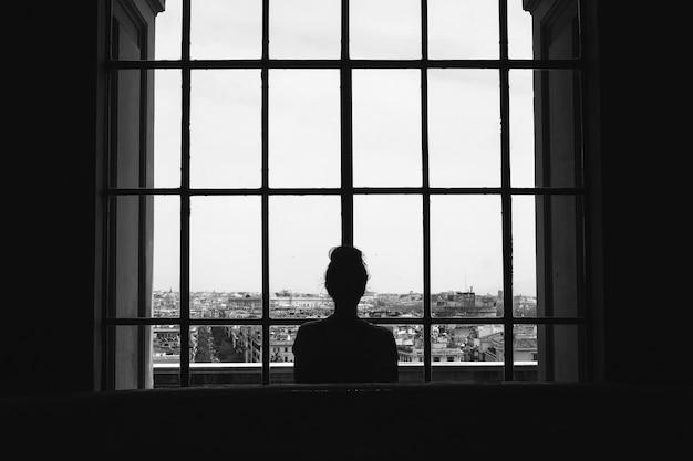 Zwart-witfoto van een eenzaam vrouwtje dat voor de ramen naar de gebouwen kijkt Gratis Foto