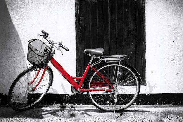 Zwart-witte foto van rode fiets - vintage filmkorrelfilter effect stijlen Premium Foto