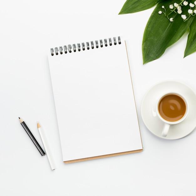 Zwart-witte kleurpotloden, lege spiraalvormige blocnote, koffiekop en bladeren op bureau Gratis Foto