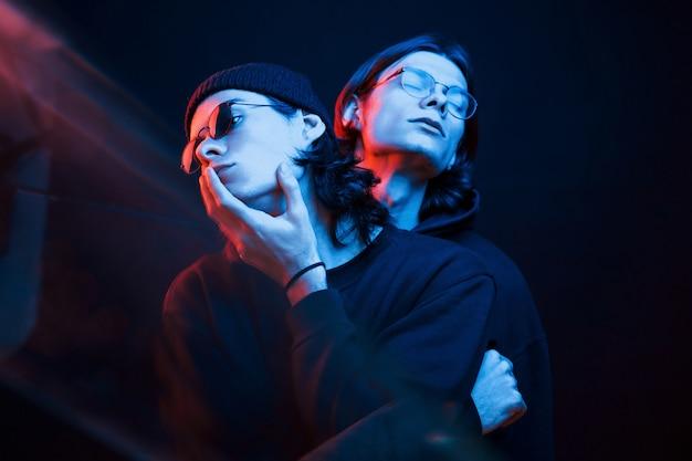 Zwarte achtergrond. portret van tweelingbroers. studio opname in donkere studio met neonlicht Premium Foto