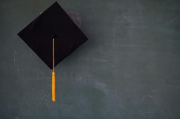 Zwarte afgestudeerde hoed op het schoolbord Premium Foto