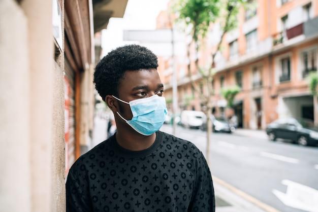 Zwarte afro-amerikaanse jongen die door de straat loopt met een blauw gezichtsmasker en zichzelf beschermt tegen de coronavirus-pandemie covid-19 Premium Foto