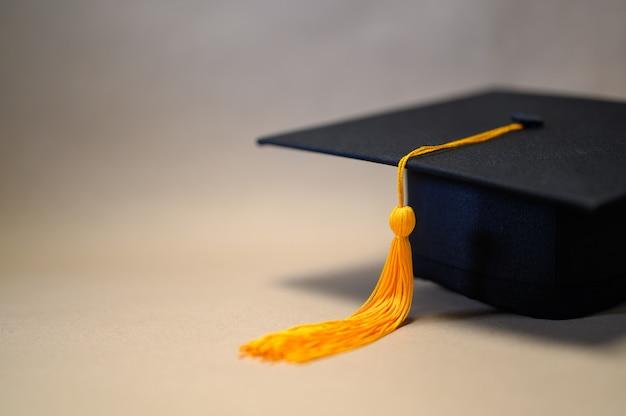 Zwarte afstuderen hoed geplaatst op bruin papier Premium Foto