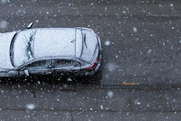 Zwarte auto op de weg onder de sneeuw in de lente in nieuw zagreb, kroatië Gratis Foto