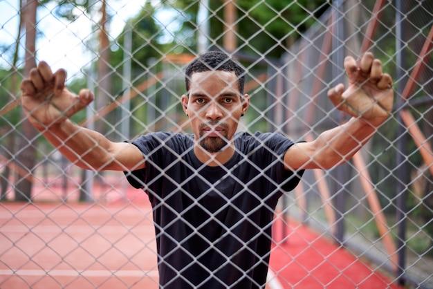 Zwarte basketbalspeler die het hek van de kettingslink met handen houdt Premium Foto