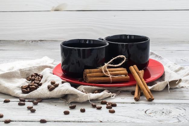 Zwarte beker, houten wand, drank, kerstochtend, koffiebonen, kaneelstokjes Gratis Foto