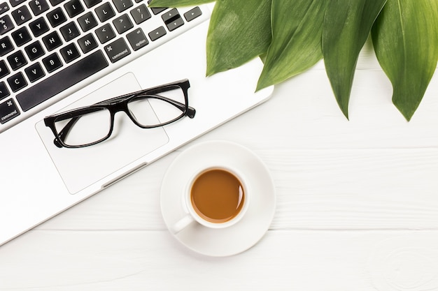 Zwarte bril en bladeren op een opengeklapte laptop met een koffiekopje op houten bureau Gratis Foto