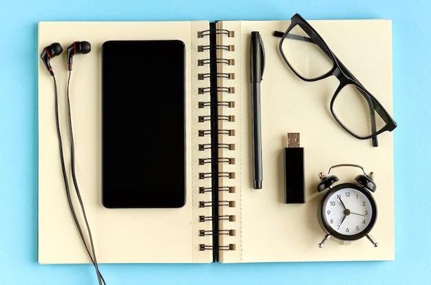 Zwarte bril, mobiel, papieren notitieblok, wekker en koptelefoon op blauwe ondergrond. Premium Foto