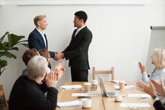 Zwarte ceo en witte zakenman handen schudden op groepsbijeenkomst Gratis Foto