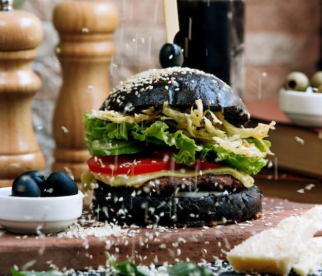 Zwarte cheeseburger gegarneerd met sesamzaadjes Gratis Foto