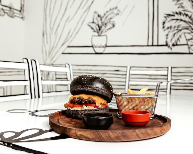 Zwarte cheeseburger met patat Gratis Foto