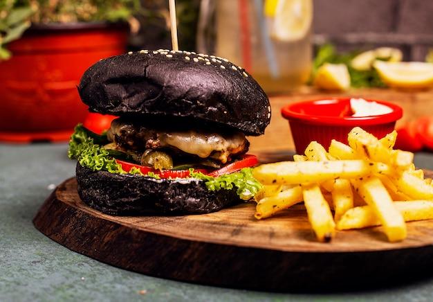 Zwarte chocolade pan rundvlees kaas hamburger met groenten fastfood, franse frietjes en ketchup. Gratis Foto
